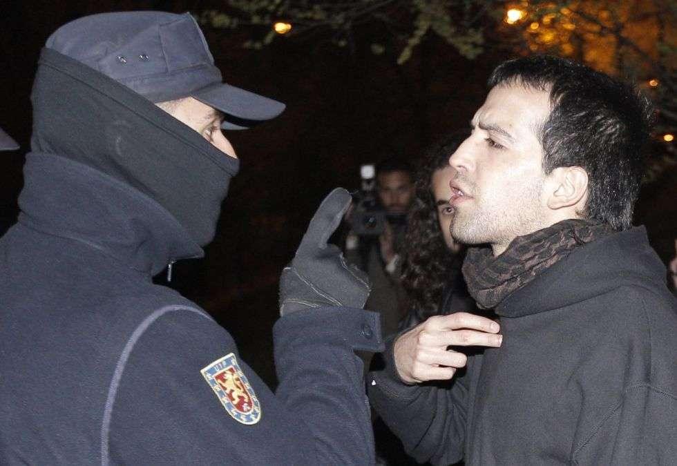 Un policía se dirige a un miembro de los piquetes que se concentraron en la entrada de las cocheras de la EMT en el barrio de La Elipa.